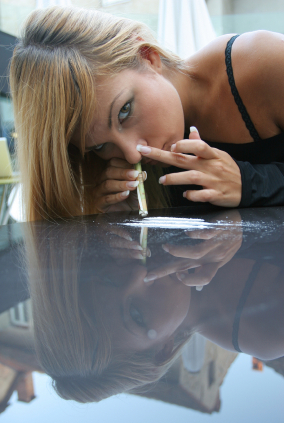 A woman sheepishly snorting cocaine